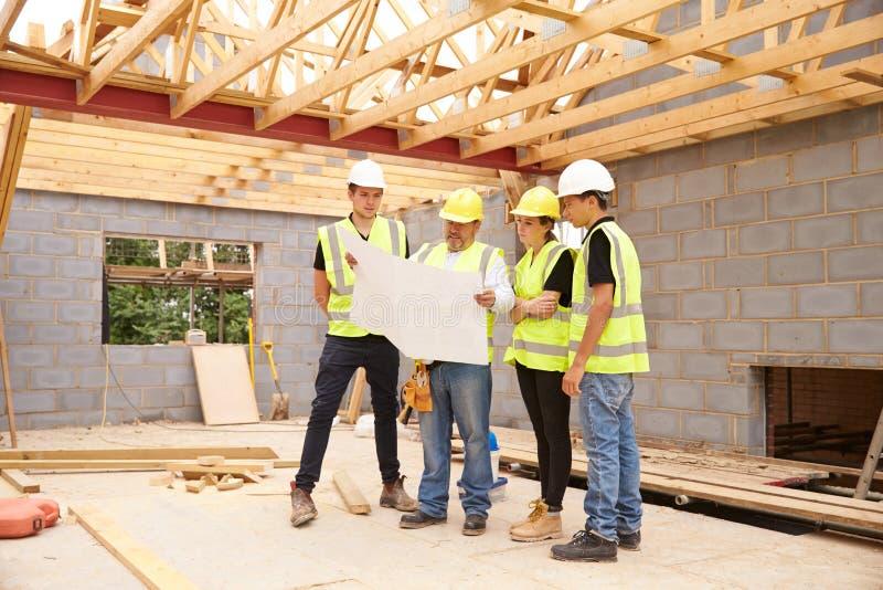 Bouwer On Building Site die Plannen met Leerlingen bekijken stock afbeeldingen