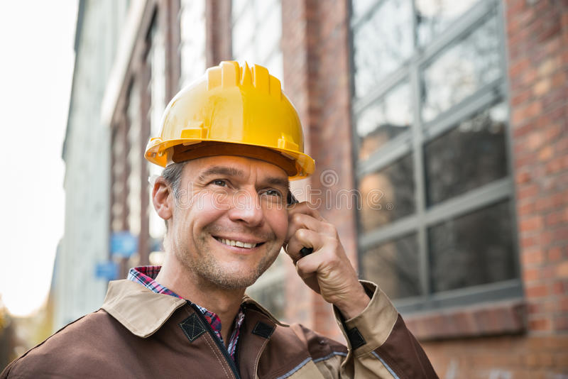 Bouwer die bouwvakker dragen die op walkie-talkie spreken stock afbeelding
