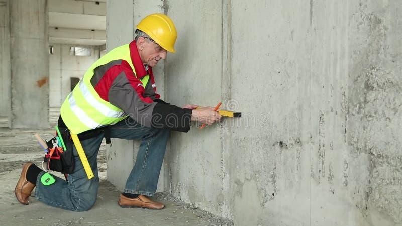 Bouwer in gele bouwvakker met niveau bij bouwterrein stock footage