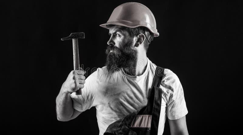Bouwer in helm, hamer, manusje van alles, bouwers in bouwvakker De manusje van allesdiensten Hamer het hameren de industrie, tech stock afbeeldingen