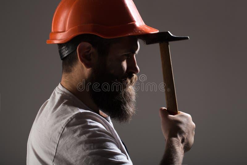 Bouwer in helm, hamer, manusje van alles, bouwers in bouwvakker Gebaarde mensenarbeider met baard, de bouwhelm, bouwvakker stock foto