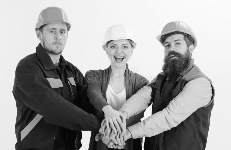 Bouwer, ingenieur, arbeider, hersteller als vriendschappelijk team De vrouw en de mannen in bouwvakkers houden samen handen royalty-vrije stock foto
