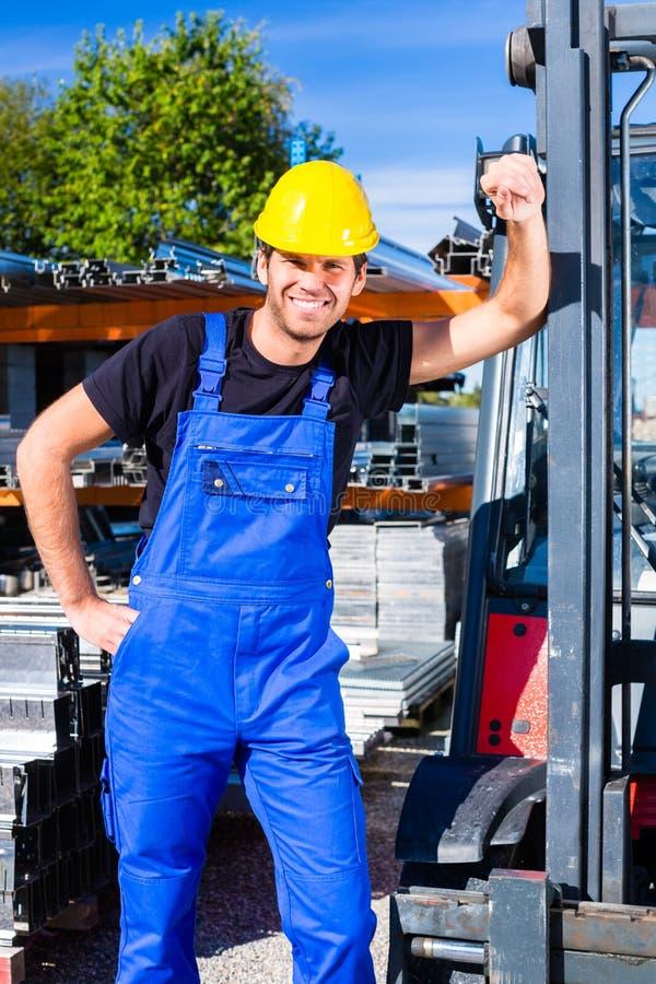 Bouwer met de vervoerder van de plaatspallet of liftvorkheftruck stock fotografie
