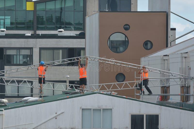 Bouwers die een metaalkader op een de bouwdak assembleren stock afbeeldingen