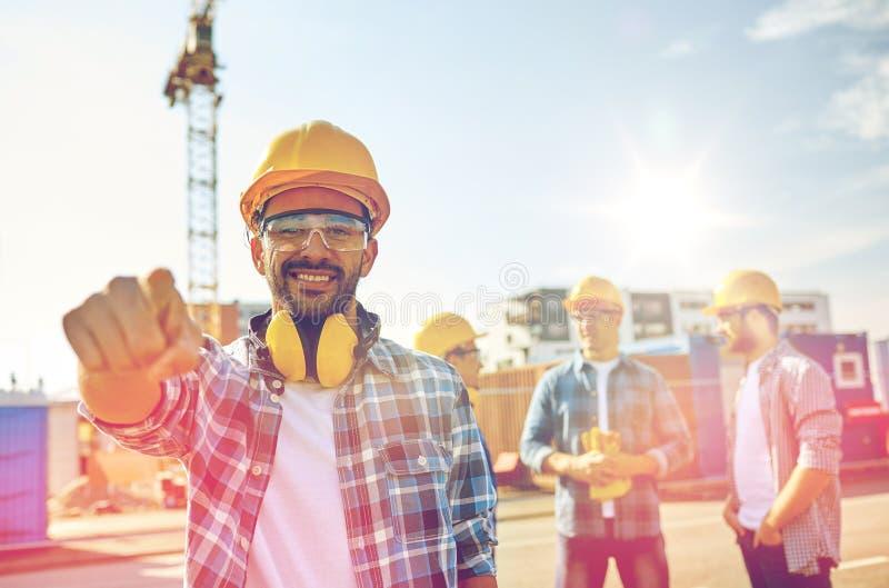 Bouwers die vinger op u bij de bouw richten stock foto