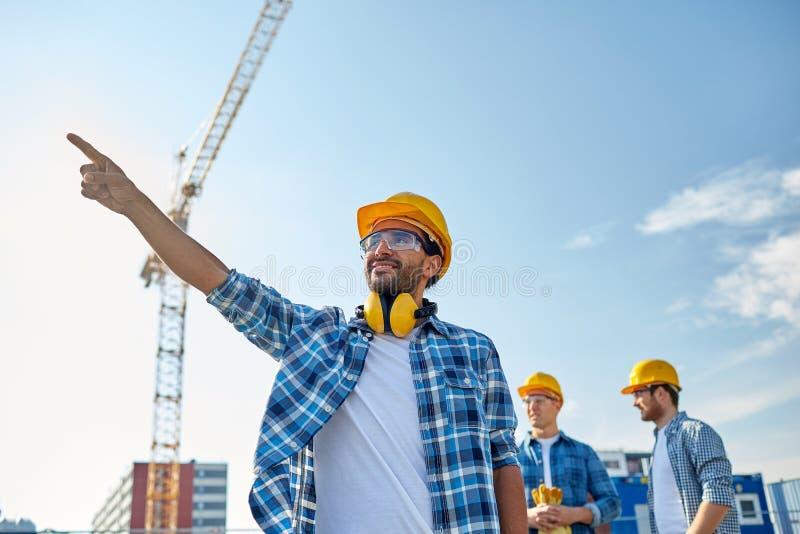 Bouwers die vinger opzij bij de bouw richten stock foto's
