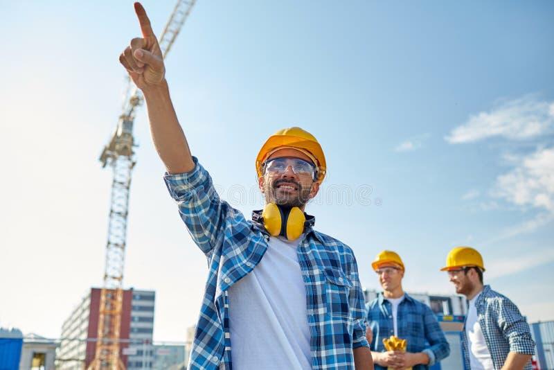 Bouwers die vinger opzij bij de bouw richten royalty-vrije stock afbeeldingen