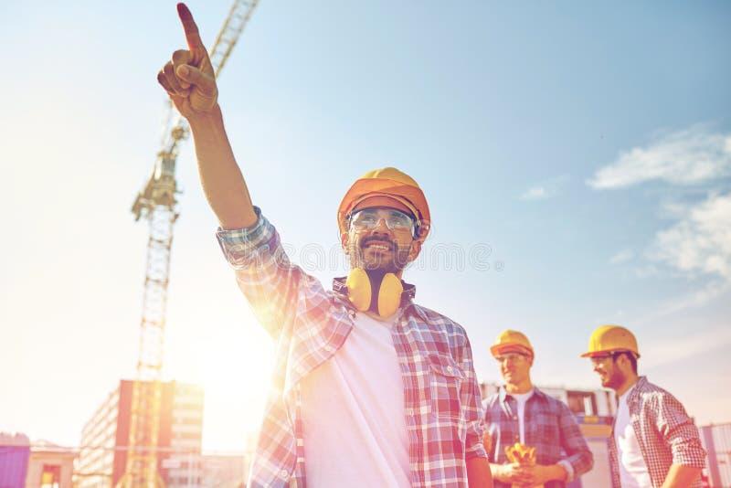 Bouwers die vinger opzij bij de bouw richten stock fotografie