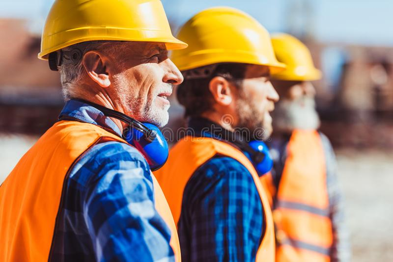 Bouwers in weerspiegelende vesten en bouwvakkers die zich bij bouwwerf, het kijken verenigen stock foto