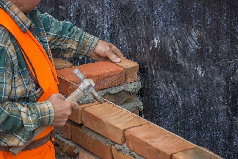 Bouwersarbeider die met metselaarshamer stevige kleibaksteen 2 leggen royalty-vrije stock foto