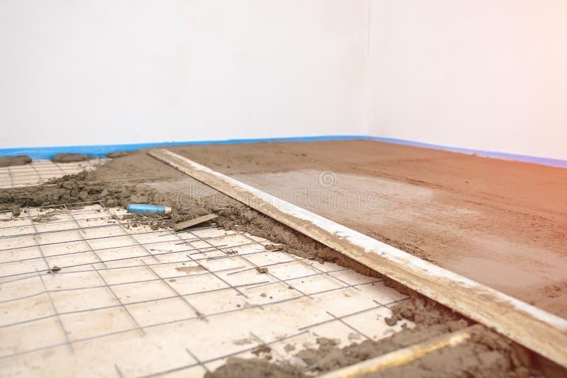Bouwersarbeider het pleisteren beton bij vloer van huisbouw royalty-vrije stock afbeeldingen