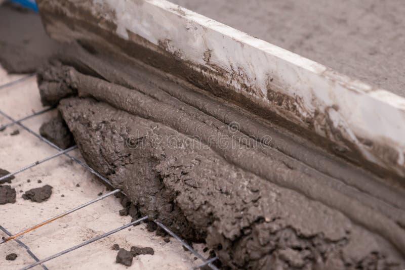 Bouwersarbeider het pleisteren beton bij vloer van huisbouw stock afbeelding