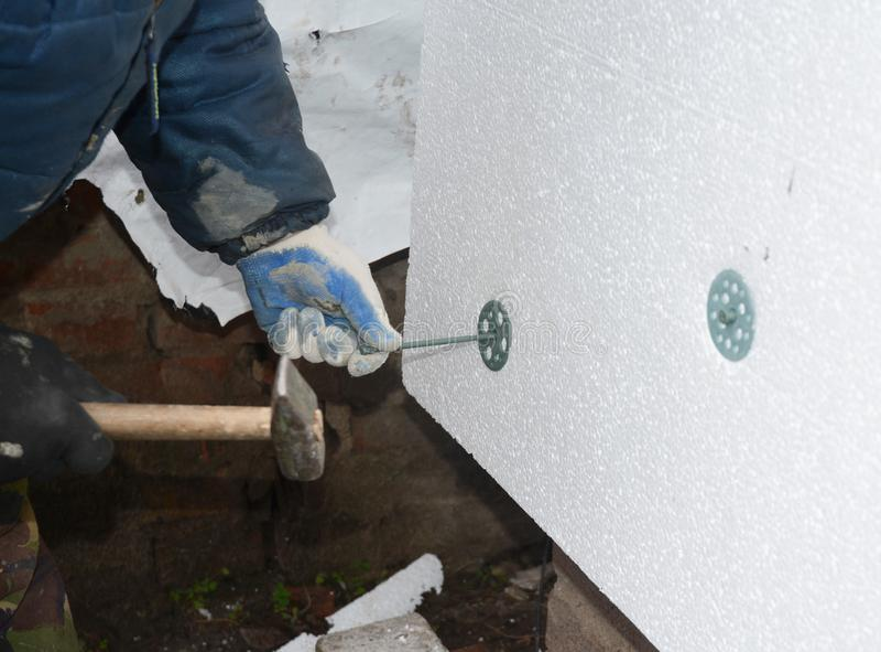 Bouwerscontractant die de stijve raad van de storaxschuimisolatie met plastic spijkers en hamer voor huisenergie installeren - be stock foto