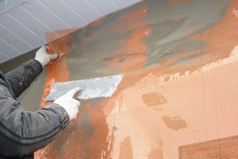 Bouwerscontractant het pleisteren muur met spatel, glasvezelnetwerk, pleisternetwerk na schuim stijve isolatie royalty-vrije stock foto