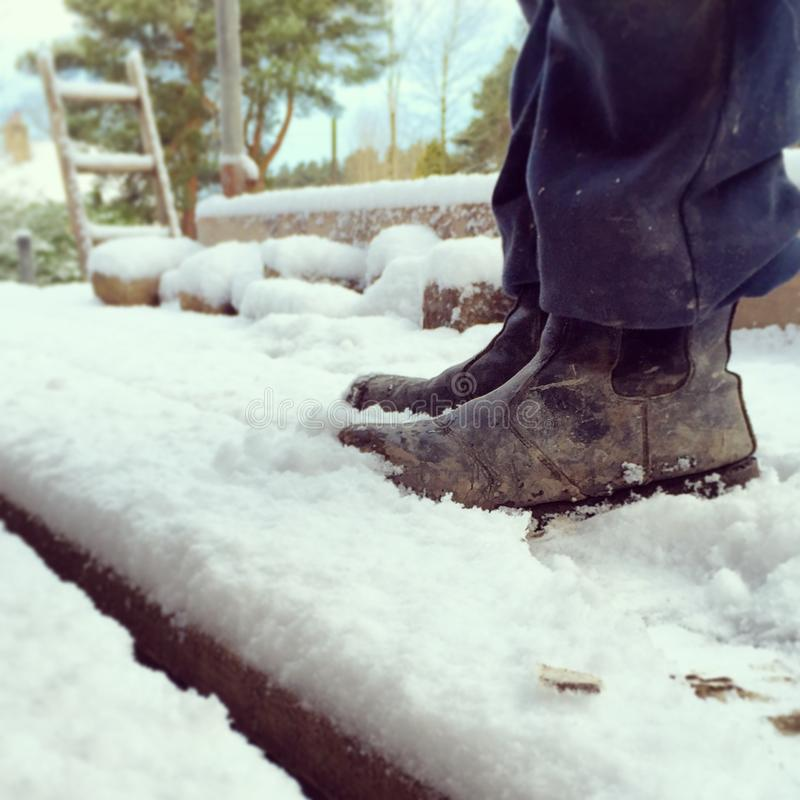 Bouwerslaarzen op sneeuw behandelde steiger royalty-vrije stock afbeelding