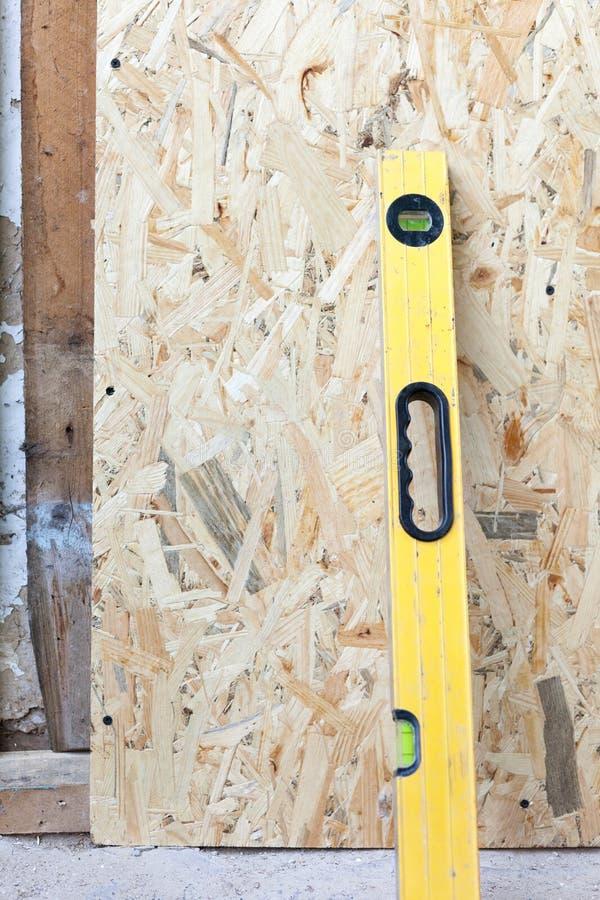 Bouwersniveau dichtbij dichte omhooggaand van de houtvezelplaatmuur stock afbeelding