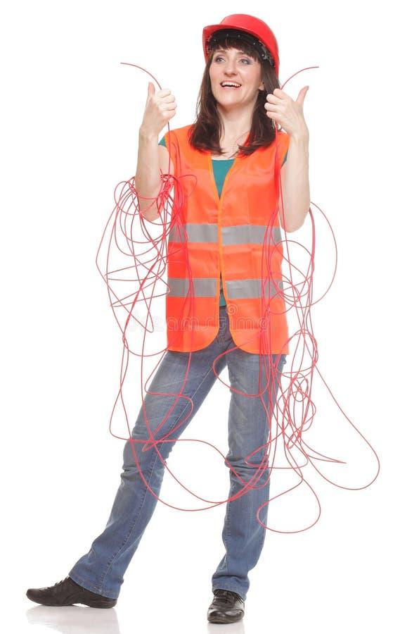 Bouwersvrouw in weerspiegelend vest en verwarde rode kabel stock fotografie