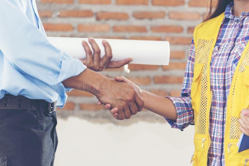 Bouwgroepswerk het schudden handen met ingenieur en voorman in bouwwerf stock afbeelding