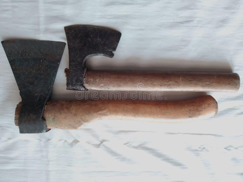 Bouwhulpmiddelen, 2 kleine assen met houten handvatten, een witte achtergrond stock fotografie