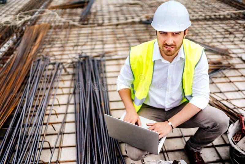 bouwingenieur die aan laptop werken, veiligheidsequipement dragen en arbeiders coördineren royalty-vrije stock fotografie