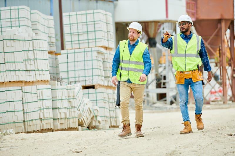 Bouwinspecteurs die op bouwwerf lopen stock afbeelding