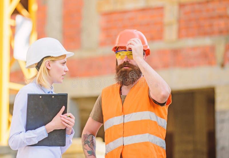 Bouwinspectie, correcties en boetes Het concept van de veiligheidsinspecteur Bespreek vooruitgangsproject Inspecteur en stock afbeeldingen