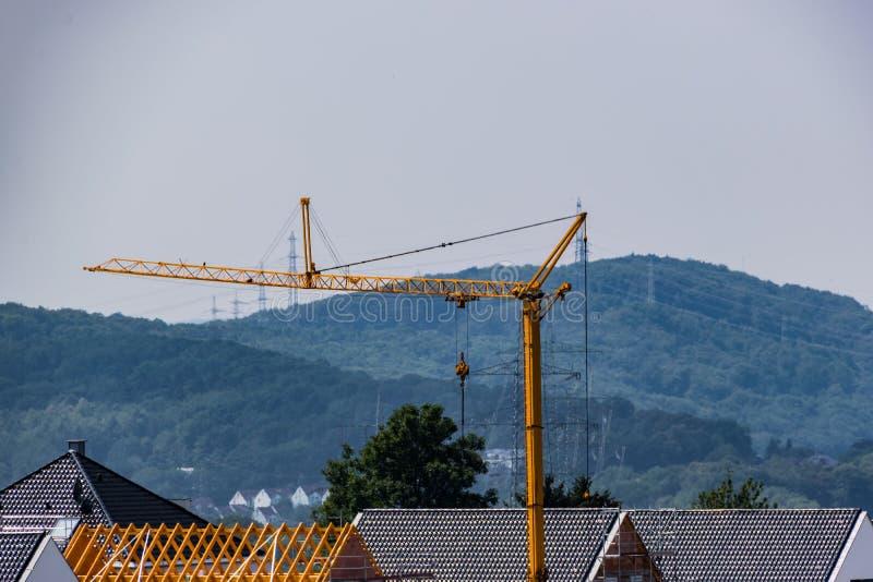 Bouwkraan over de daken van de stad stock foto's