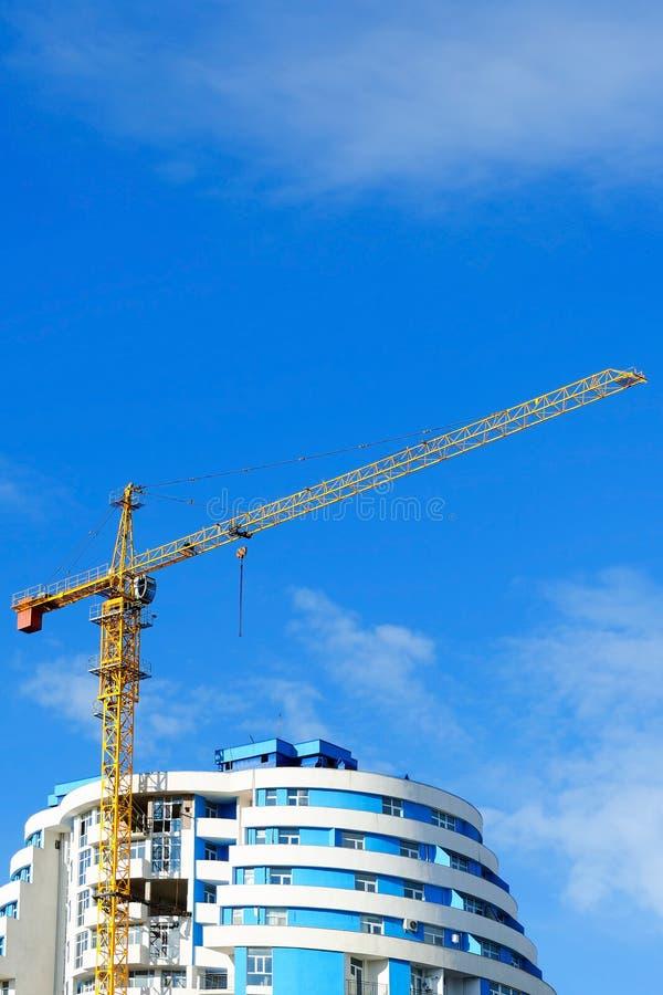 Bouwkraan over het dak van een woonhigh-rise gebouw royalty-vrije stock afbeeldingen