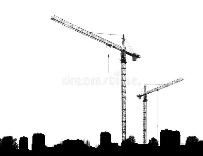 Bouwkranen en silhouettengebouwen stock foto