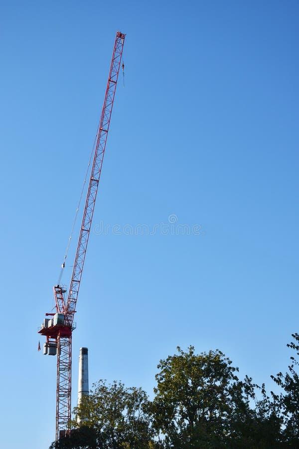 Bouwkranen tegen een blauwe hemelachtergrond stock afbeeldingen