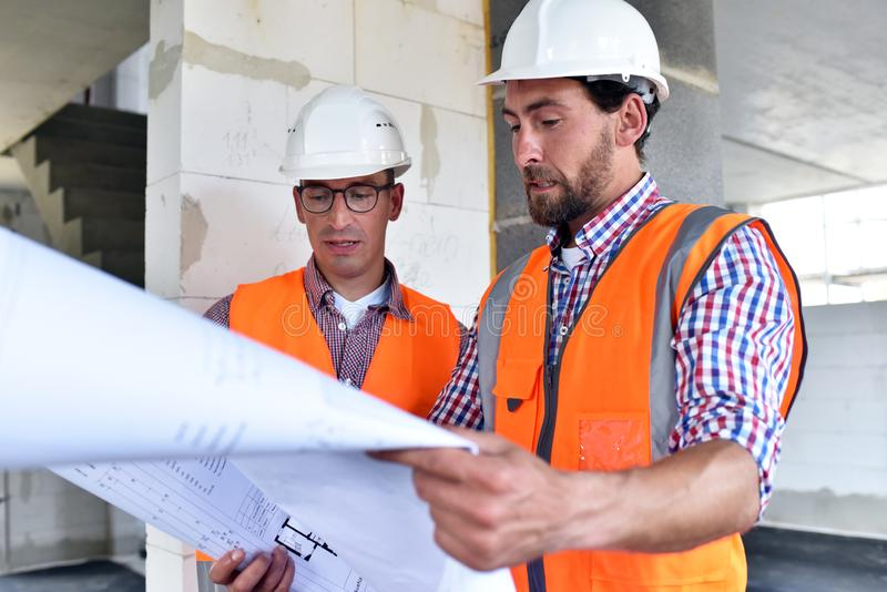Bouwmanager en architect op plaats tijdens de bouw van een huis - planning en controle op plaats - groepswerk stock fotografie
