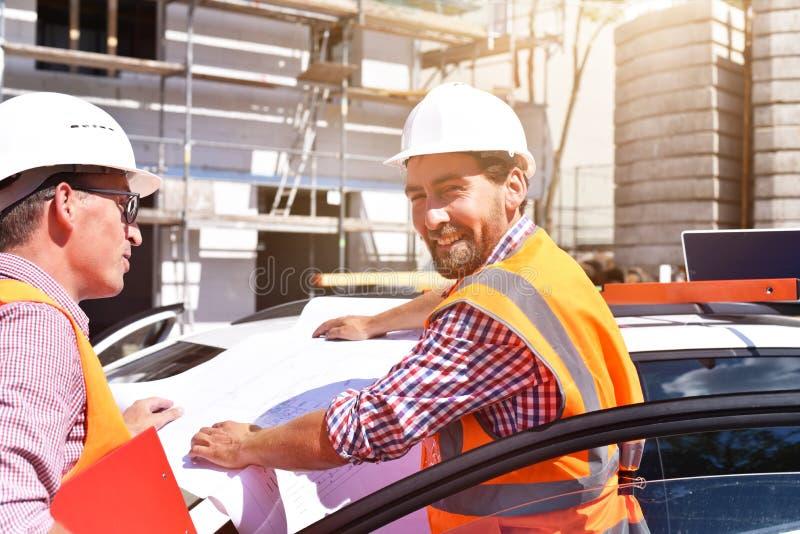 Bouwmanager en architect op plaats tijdens de bouw van een huis - planning en controle op plaats - groepswerk royalty-vrije stock afbeelding