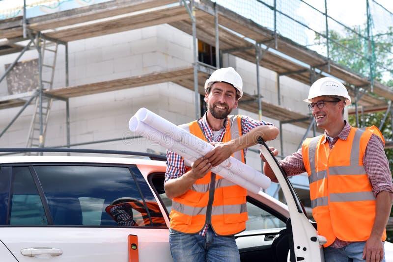 Bouwmanager en architect op plaats tijdens de bouw van een huis - planning en controle op plaats - groepswerk royalty-vrije stock afbeeldingen