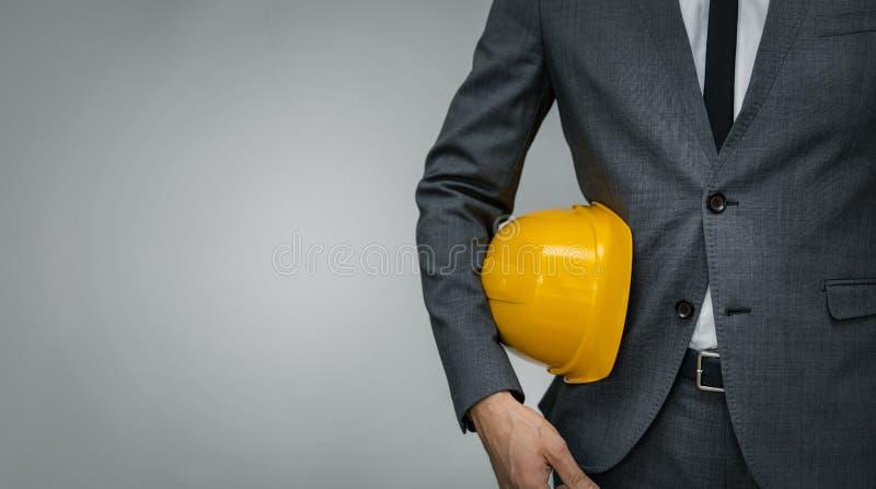 Bouwnijverheid - zakenman met geel hard onderliggend onderliggend op grijze achtergrond royalty-vrije stock foto