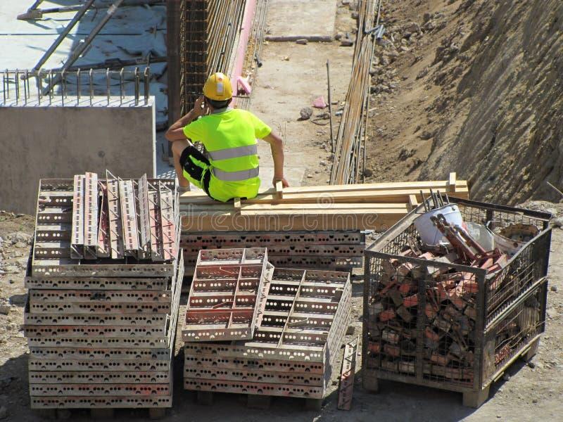 Bouwvakker in de bouw van moderne woningbouw Een arbeider die van een mobiele telefoon roepen stock foto's
