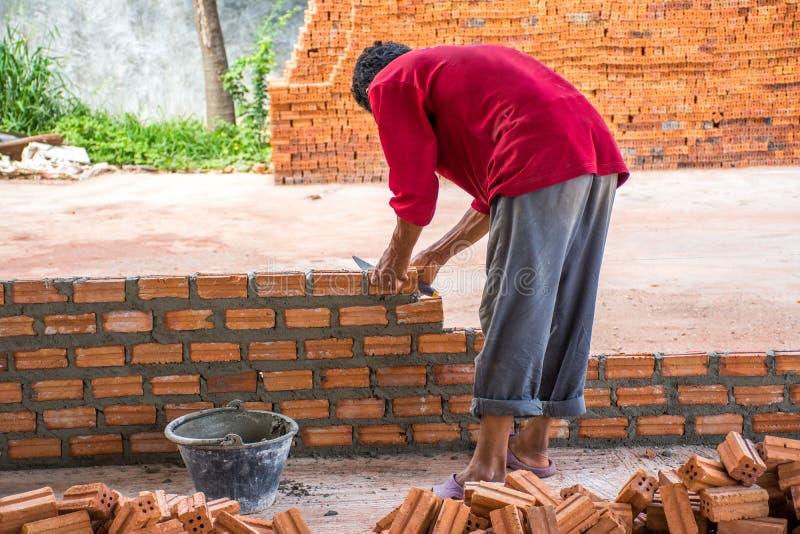 Bouwvakker die bakstenen plaatsen op cement voor de bouwexteri royalty-vrije stock fotografie