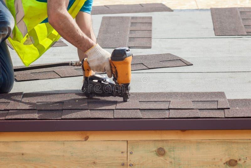 Bouwvakker die de dakspanen van het asfaltdakwerk met spijkerkanon zet op een nieuw kaderhuis stock foto's