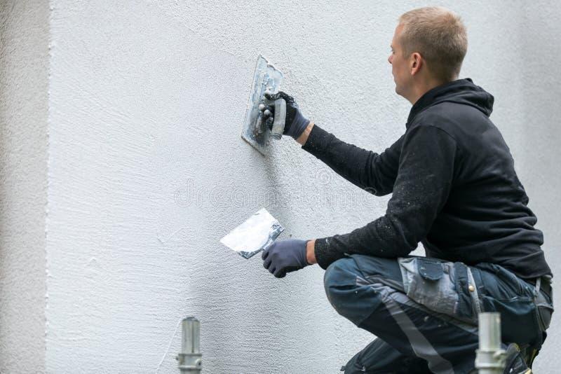 Bouwvakker die decoratief pleister op huisbuitenkant zetten stock afbeelding