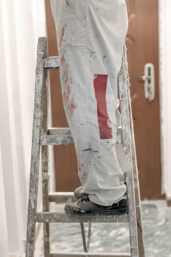 Bouwvakker die ladder voor het werken aan huisvernieuwingen gebruiken royalty-vrije stock afbeeldingen