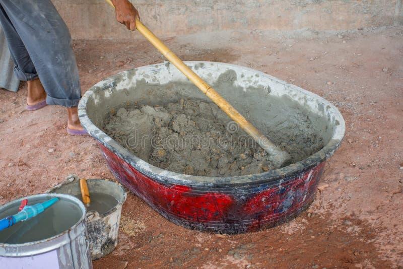 Bouwvakker die manueel beton in mixerdienblad mengen stock fotografie