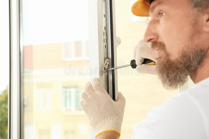Bouwvakker die nieuw venster installeren stock fotografie