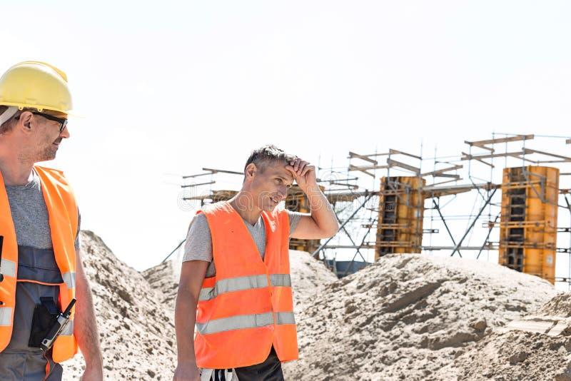Bouwvakker die vermoeid collega afvegend zweet bekijken bij plaats stock foto