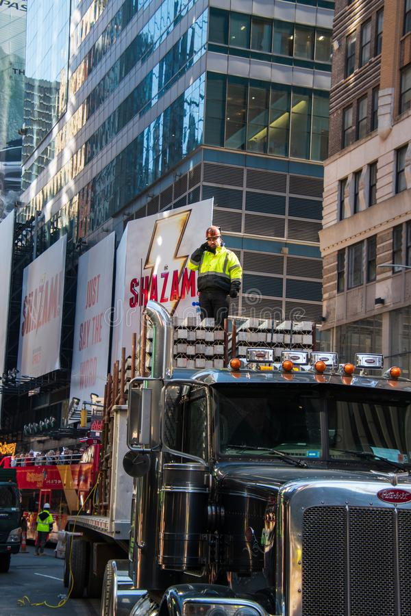 Bouwvakker die zich bovenop een concrete lading op een grote vrachtwagen op een weg in Manhattan, New York bevinden stock fotografie