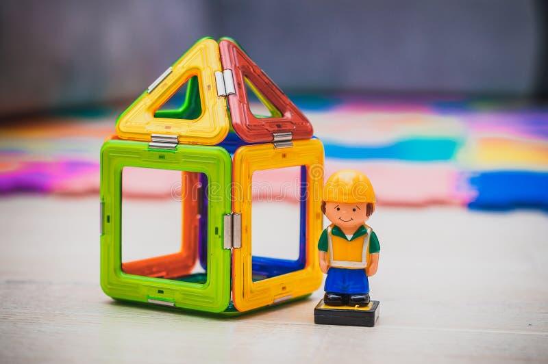 Bouwvakker en bouwnijverheidsconcept Stuk speelgoed huisminiatuur stock foto