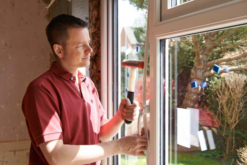 Bouwvakker Installing New Windows binnenshuis royalty-vrije stock afbeeldingen