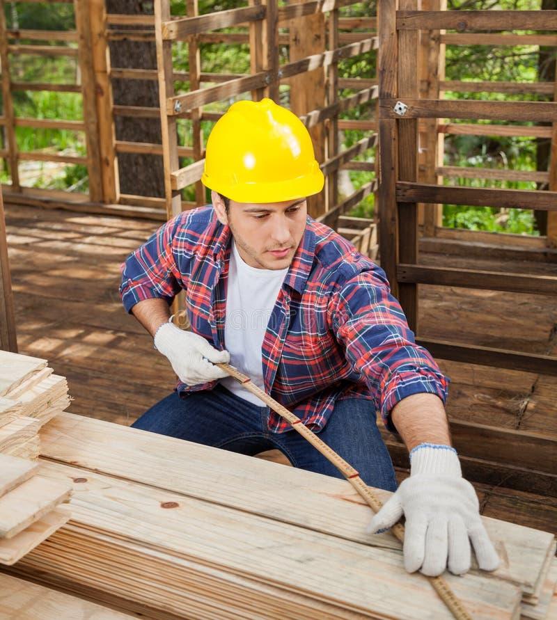 Bouwvakker Measuring Wooden Plank bij Plaats stock afbeelding