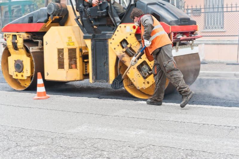 Bouwvakker met schop Stedelijke weg in aanbouw stock foto