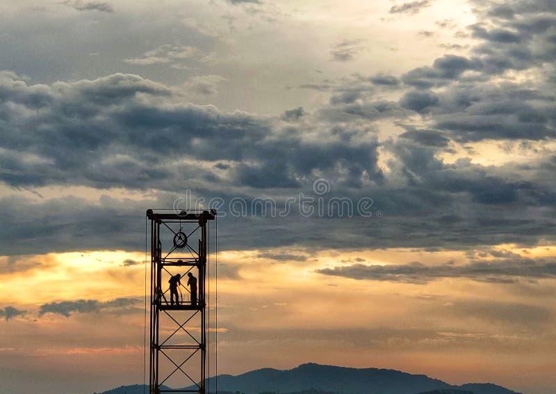 Bouwvakkers die bij zonsondergang werken stock illustratie