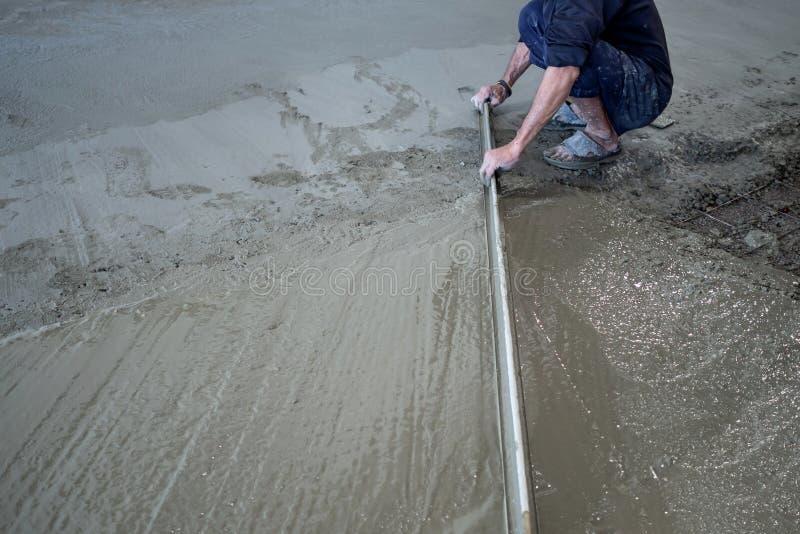 Bouwvakkers die gegoten vloeibaar beton met troffels nivelleren stock foto's