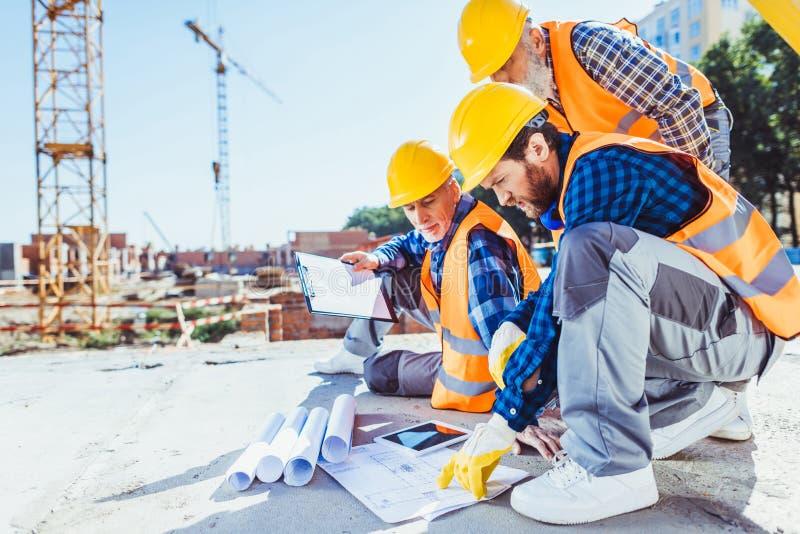 bouwvakkers in eenvormige zitting op beton bij bouwwerf, het bespreken stock afbeelding